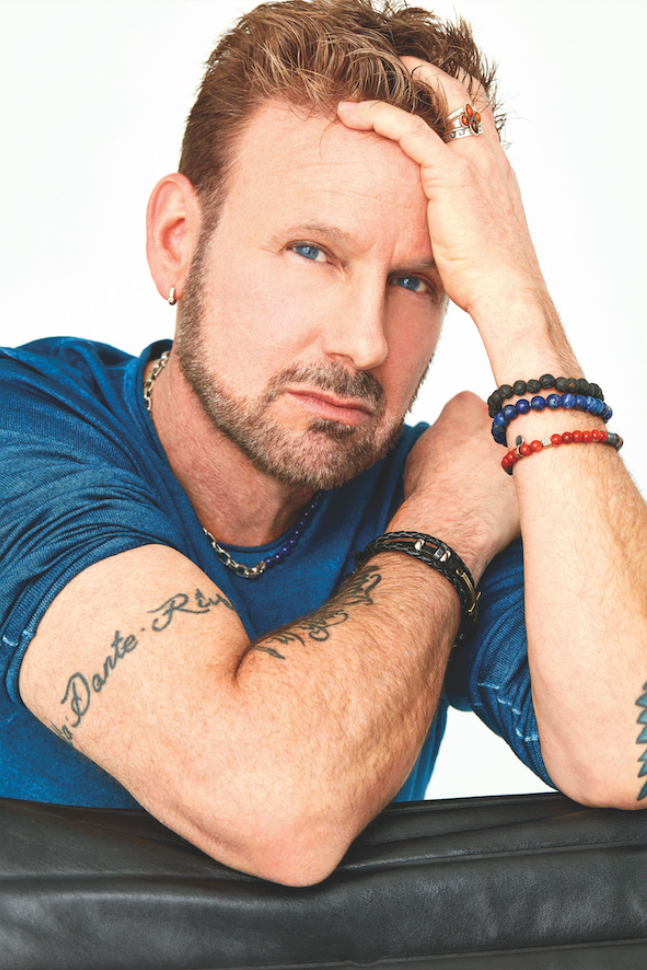 A colour photo of Corey Hart leaning against a table with his head in his hand.