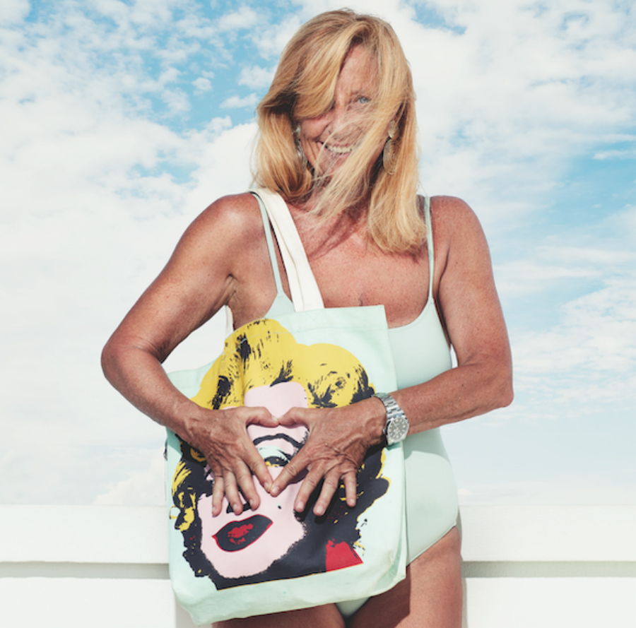 A picture of a woman in a swimsuit holding a bag with a picture of Marilyn Monroe on it.