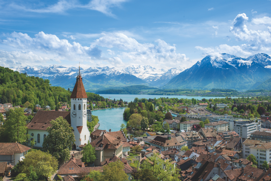 A landscape photograph of Thun, Switzerland overlooking a lake and the mountains.