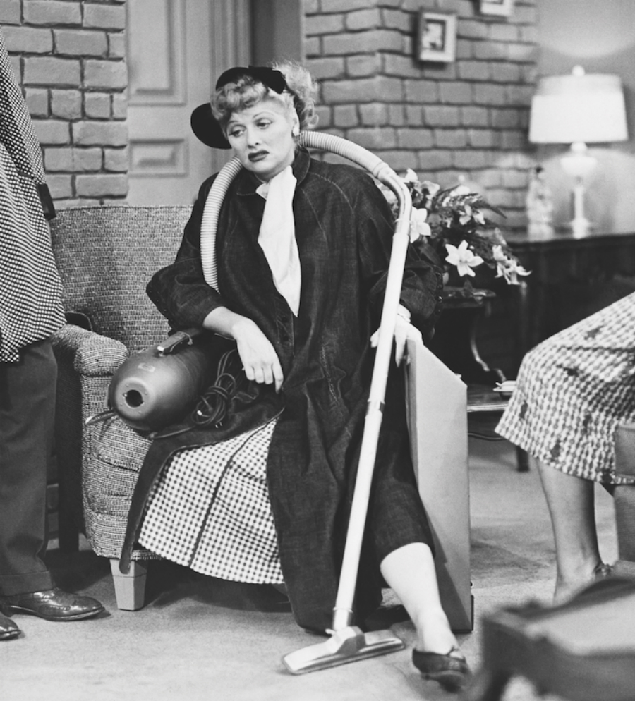 A photo of Lucille Ball looking tired on a chair with a vacuum hose draped around her shoulders.