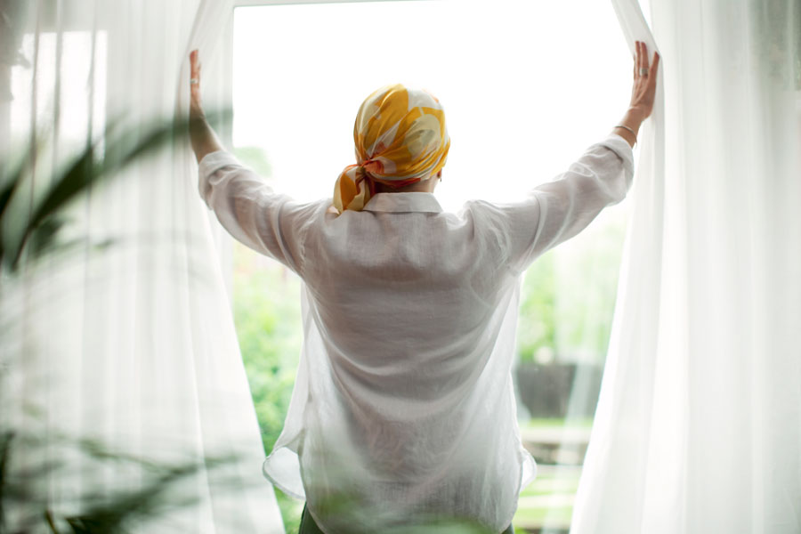 A woman wearing a bandana opens sheer drapes and looks out the window.