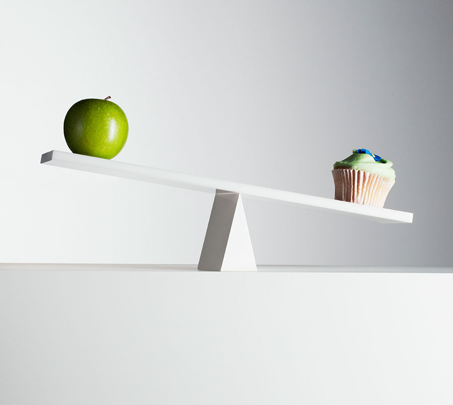 A seesaw with a green apple on one and and a cupcake on the other.