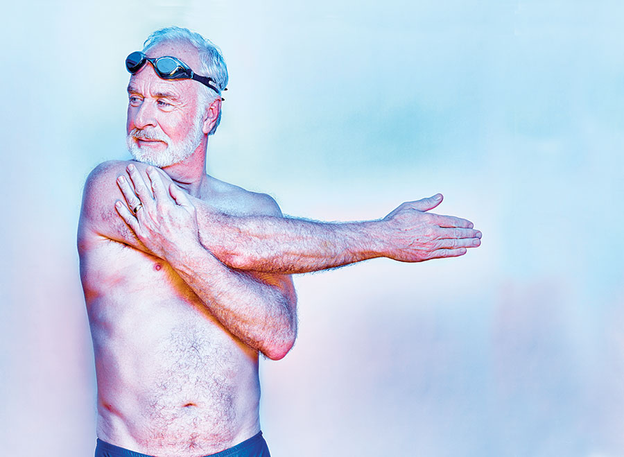 A man stretching in swimming gear