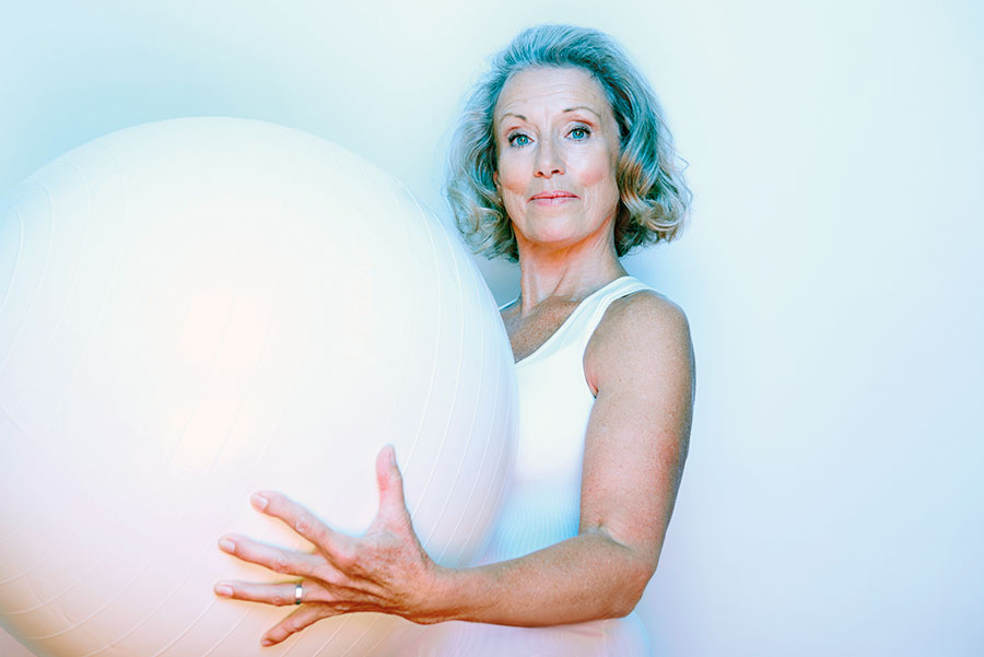 A woman holding and exercise ball