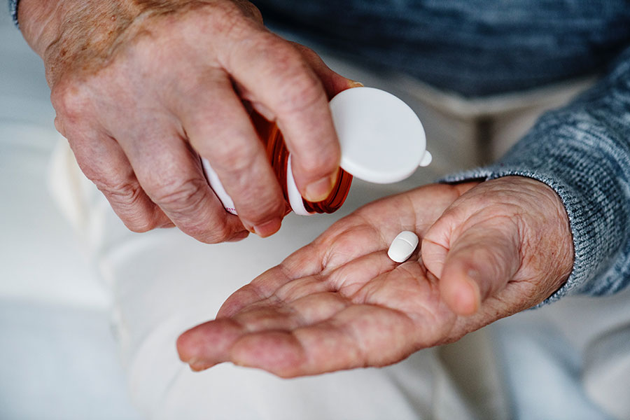 Man dispensing medication into his hand from pill bottle.