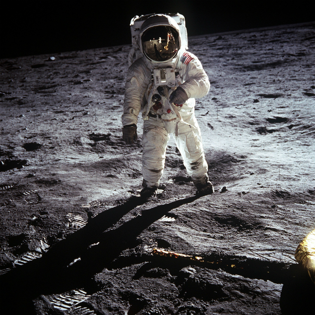 A picture of Buzz Aldrin standing on the moon. Neil Armstrong, the photographer and first man on the moon can be seen in the reflection of Aldrin's visor.