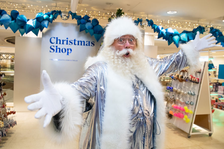 Santa, dressed in silver lame, in front of the Selfridges' Christmas Shop