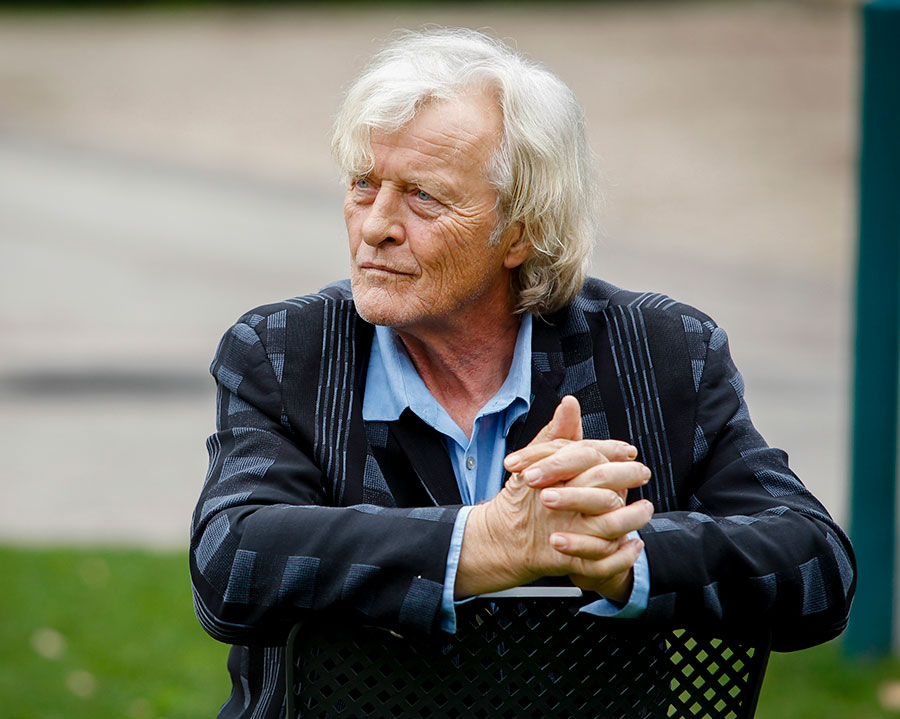 Rutger Hauer sitting backwards on a chair with his hands resting on the backrest.
