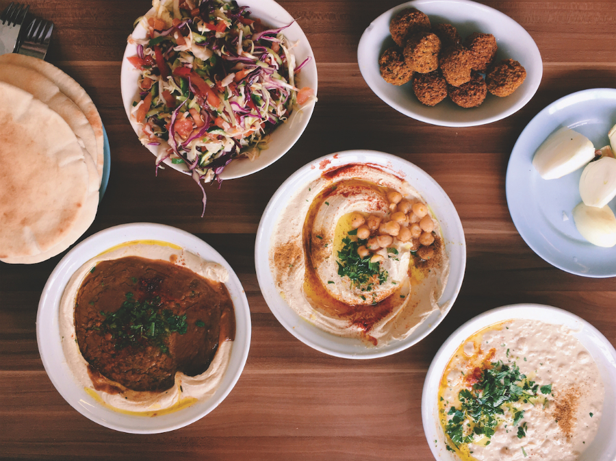 A picture of various dishes of food, including hummus.