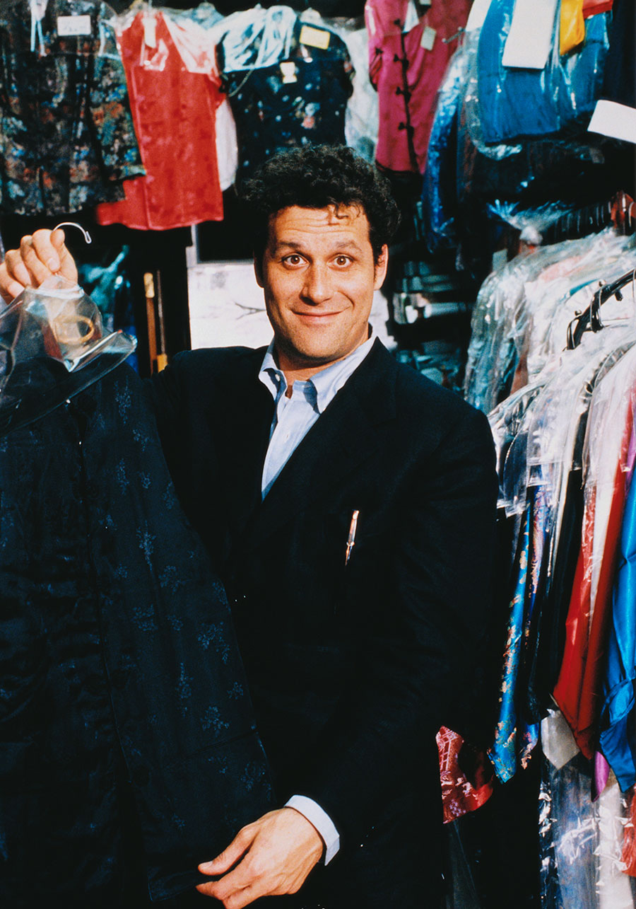 Isaac Mizrahi holding up a garment surrounded by clothes racks.