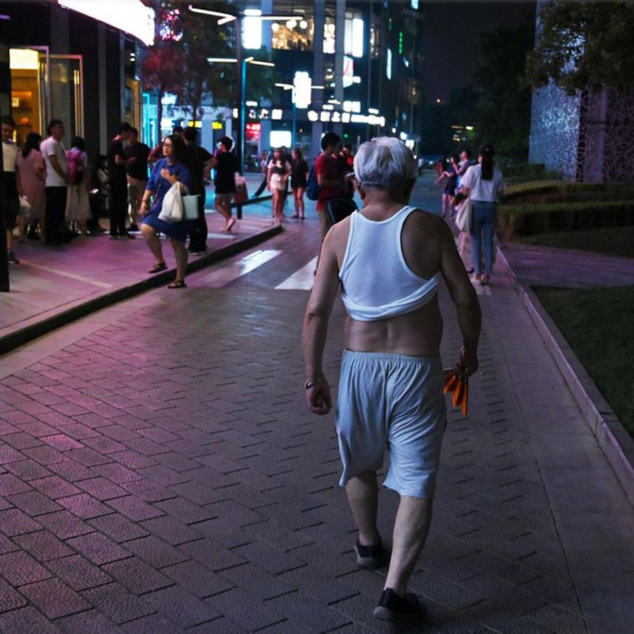Man walking in China with his stomach exposed