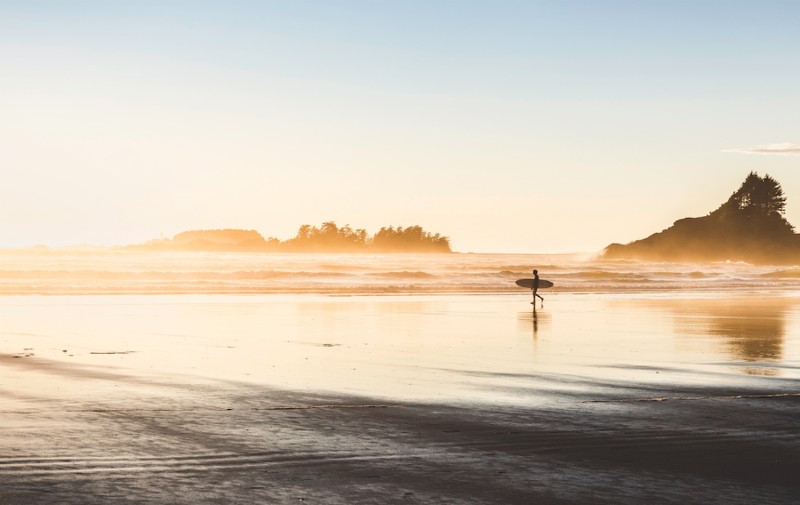 A photo of a surfer walking on the beach near sunset.