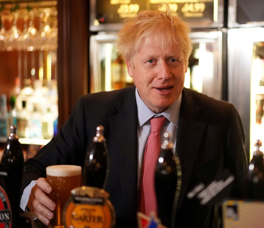 Boris Johnson holds a pint of beer behind the bar during his visit to JD Wetherspoon's Metropolitan Bar in London, on July 10, 2019.