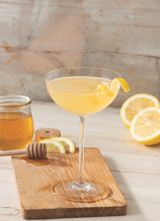 A Ungava Bee's Knees cocktail garnished with a twist of lemon.