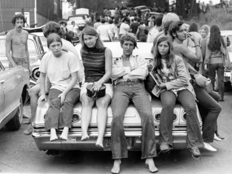 A photo of a group of people sitting on the hood of a car.