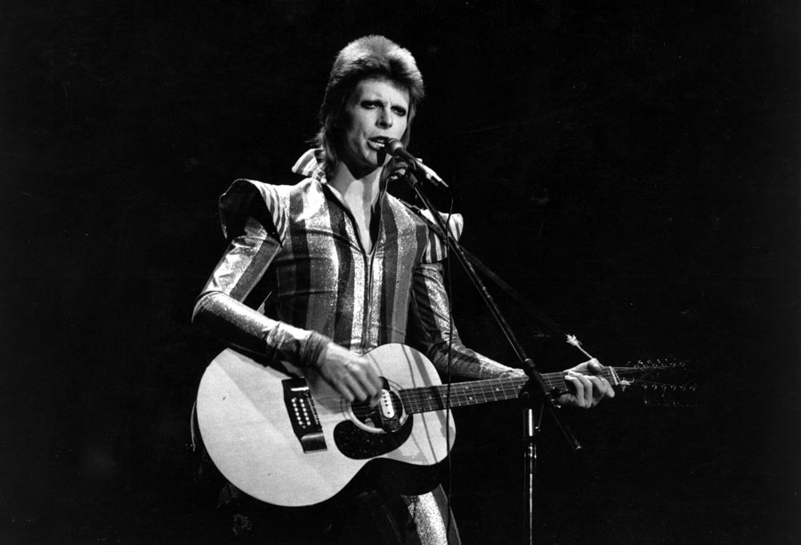 David Bowie as Ziggy Stardust on stage playing his guitar.