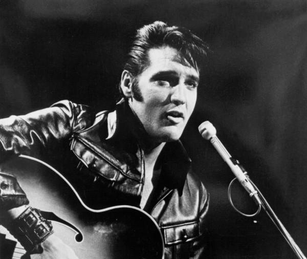 Elvis Presley strumming his guitar as he sings into a microphone.