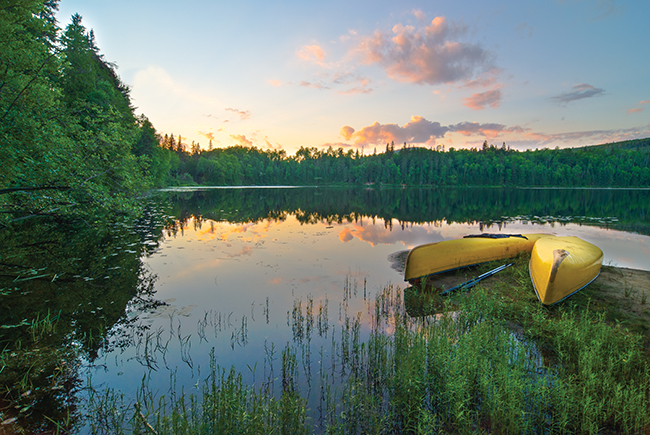 A photo of a pair of canoes by the lake during sunset at Algonquin Park.
