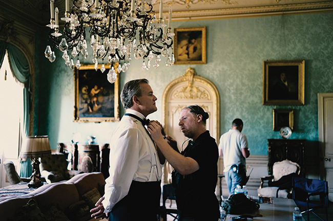 A photo of Hugh Bonneville as Lord Grantham getting into costume on the set of Downton Abbey.