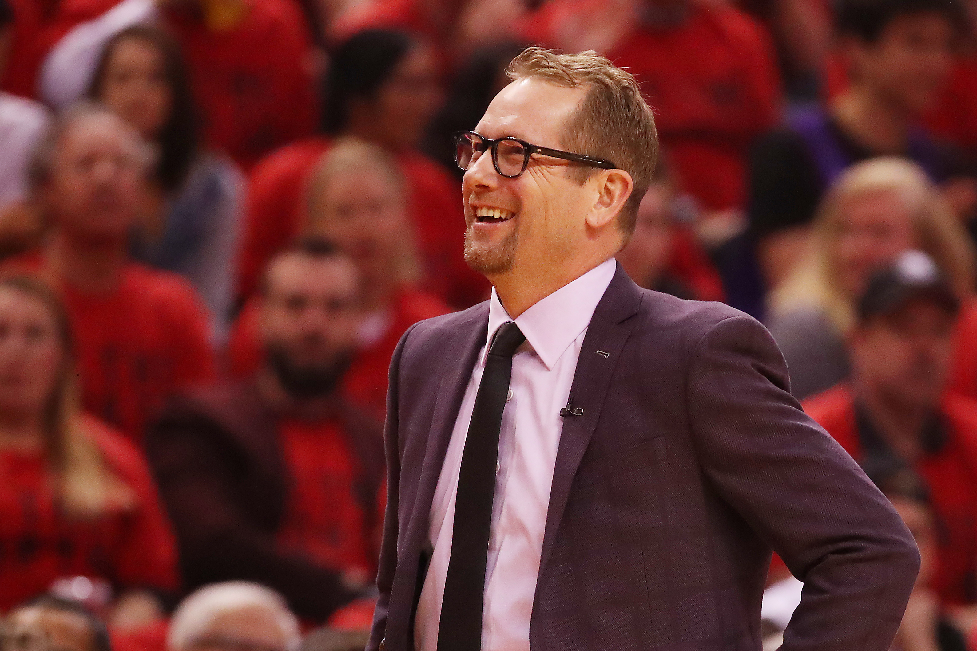 Nick Nurse with his hands on his hips looking out over the court from the sideline.