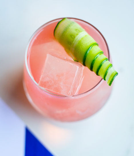 A glass filled with a watermelon cocktail and garnisheed with a ribbon of cucumber