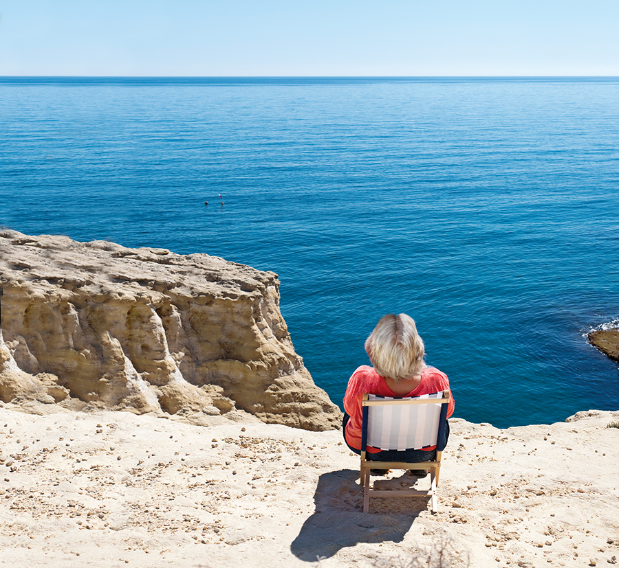 A picture of a woman sitting in chair on a rocky cliff overlooking the water.