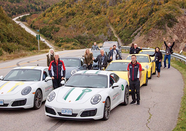 A photo of a group of people standing beside their Porsche cars on the Cabot Trail.