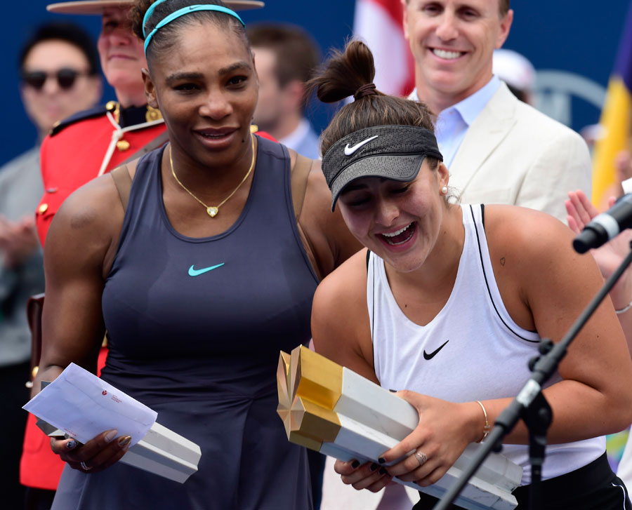Canada's Bianca Andreescu holds the winner's trophy as Serena Williams of the USA looks on