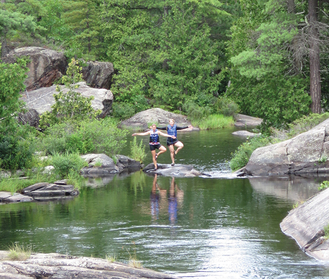 A photo of Coccimiglio and Yarmoluk holding the Tree pose at High Falls.