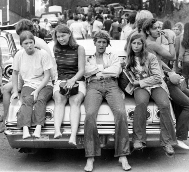 Kids sitting on the back of a car in the line to enter Woodstock in 1969.