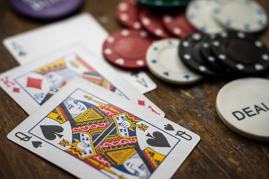 Playing cards, poker chips and a dealer chip scattered on a wooden table.