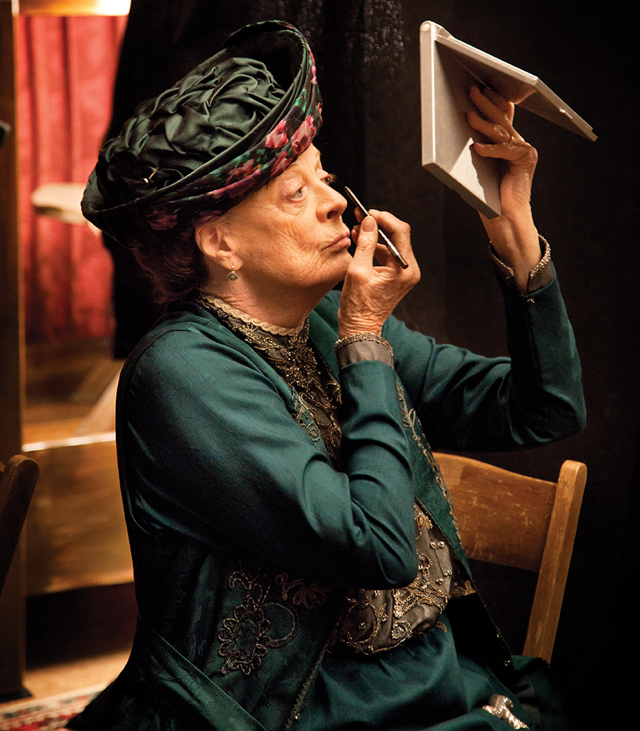 A photo of Maggie Smith doing her makeup on the set of Downton Abbey.