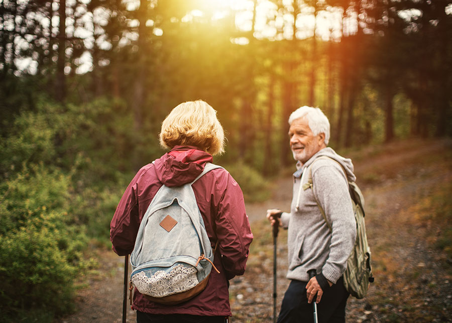 A gray haired man hiking through the forest with a woman.