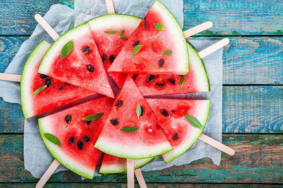 A plate of watermelon wedges on popsicle sticks