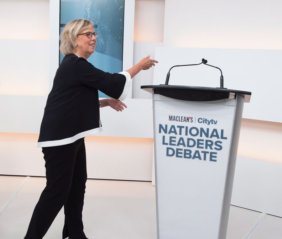 Green Party Leader Elizabeth May, left, reaches to the empty mic stand where the invited Liberal Leader Justin Trudeau turned down the debate.