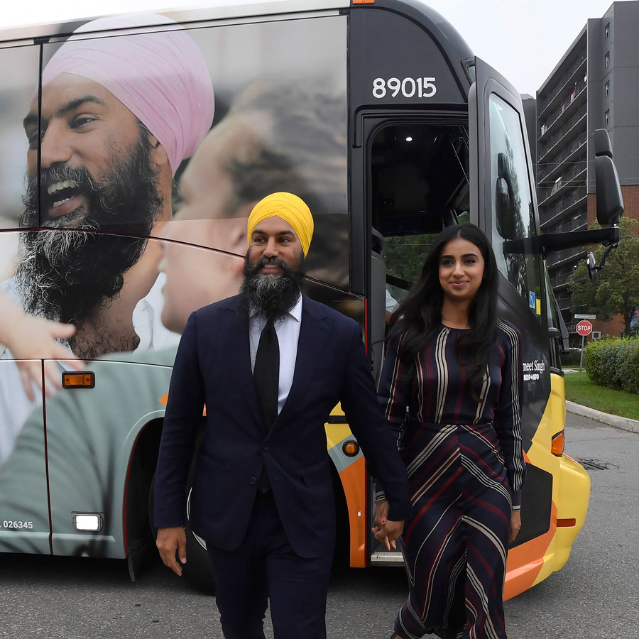 NDP Leader Jagmeet Singh and his wife Gurkiran Kaur Sidhu stand by his campaign bus in London, Ont., Wednesday, Sept.11, 2019.