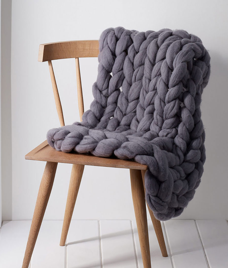 picture of a knitted blanket draped over a wooden chair