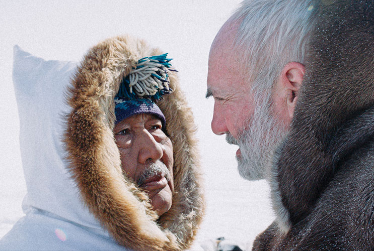 Indigenous man in parka face-to-face with a white man with white hair and beard.