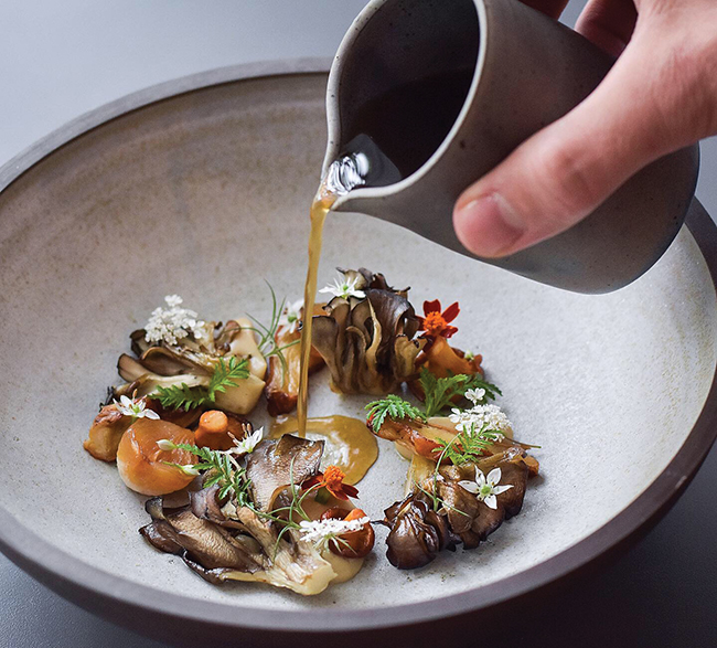 A picture of Grilled and roasted wild mushrooms, chared onions and foraged herbs with mushroom dashi broth from Est.
