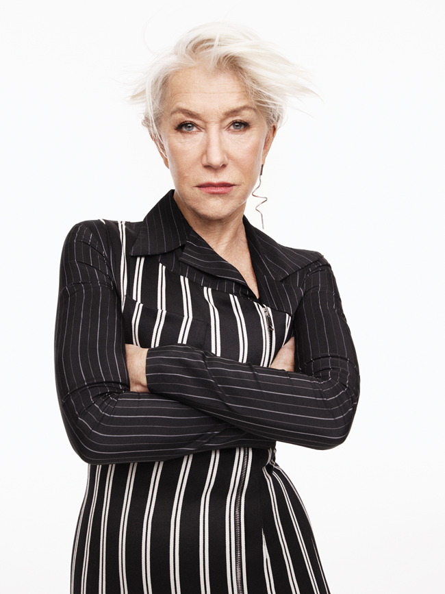 A photo of Helen Mirren in black and white striped top with arms crossed.