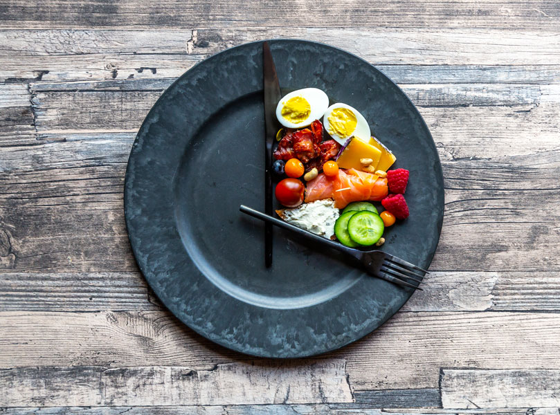 A plate with a hard boiled egg, tomatoes and a variety of vegetables filling a quarter of it.