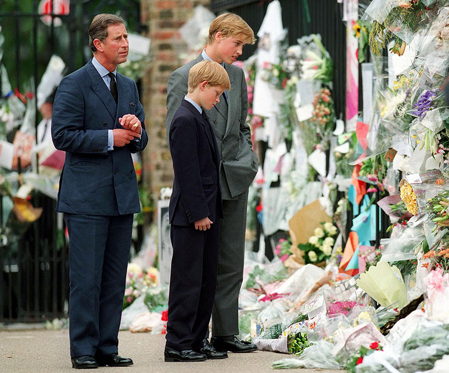 The Prince of Wales, Prince William and Prince Harry look at floral tributes to Diana, Princess of Wales outside Kensington Palace on September 5, 1997 in London, England.