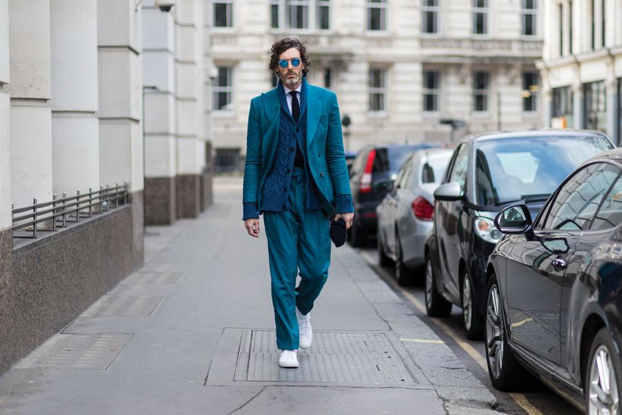 Man in aqua blue suit wearing white sneakers.