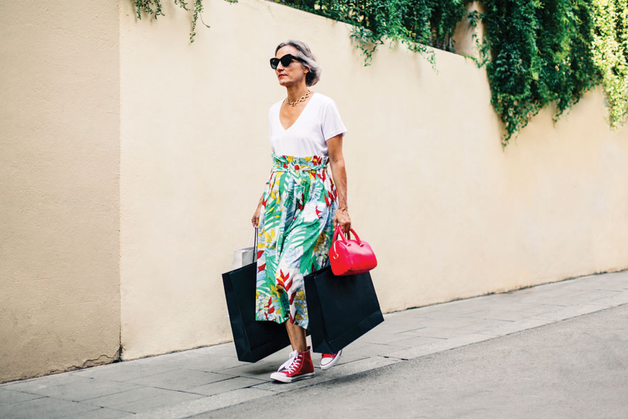 Woman in bright coloured floral long skirt wearing red chuck sneakers.