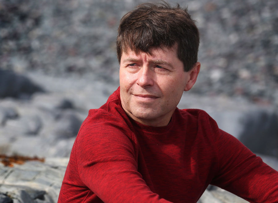 Giller Prize finalist Michael Crummey poses for a picture on Middle Cove Beach, just outside St. John's. NL.