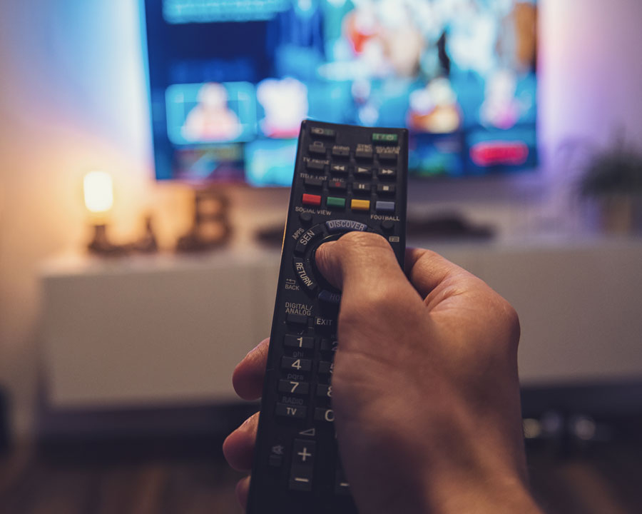 A hand holding a remote toward a television.