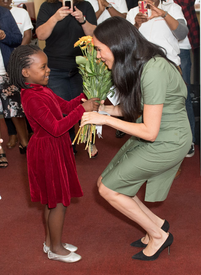 Meghan Markle accepts flower from a child a an Action Aid event during her royal tour of South Africa.