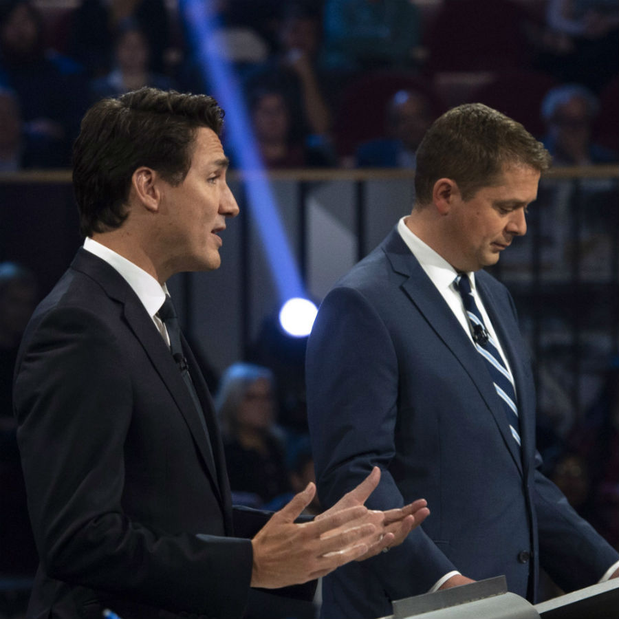 Conservative leader Andrew Scheer makes notes as Liberal leader Justin Trudeau speaks during the Federal leaders debate in Gatineau, Que. on Monday, October 7, 2019. THE CANADIAN PRESS/Sean Kilpatrick