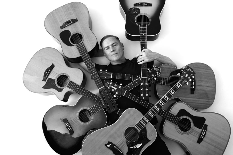 Bryan Adams lying on his back surrounded by acoustic guitars.
