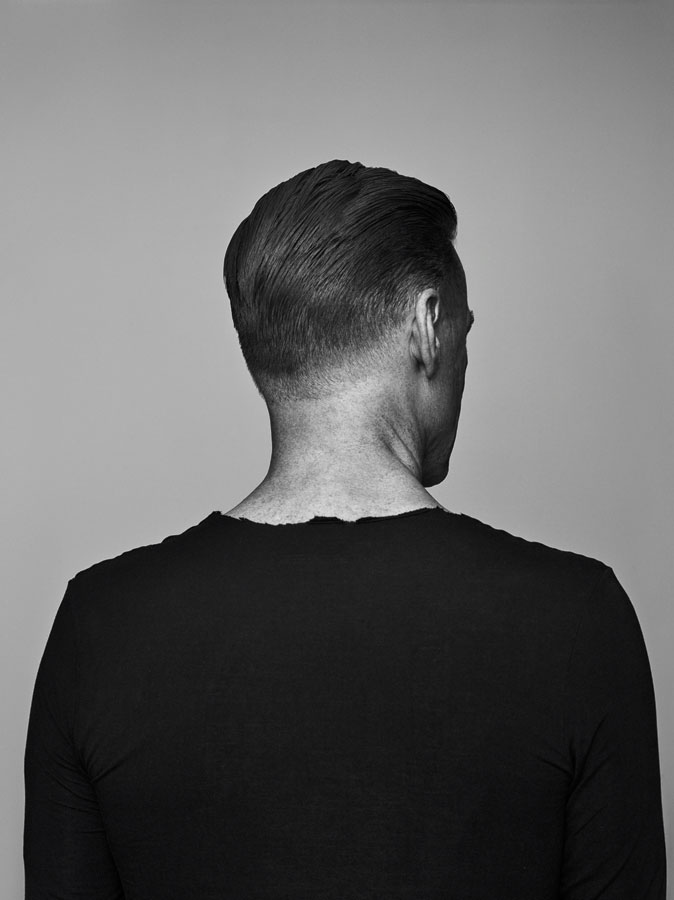 A black and white photo of Bryan Adams in a black shirt with his back turned.